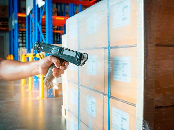 BACO Logistic - Duesseldorf - Kontraktlogistik - Lager - Transport - Service - Lagerarbeiter scannt Barcode einer Sendung im Auslieferungslager